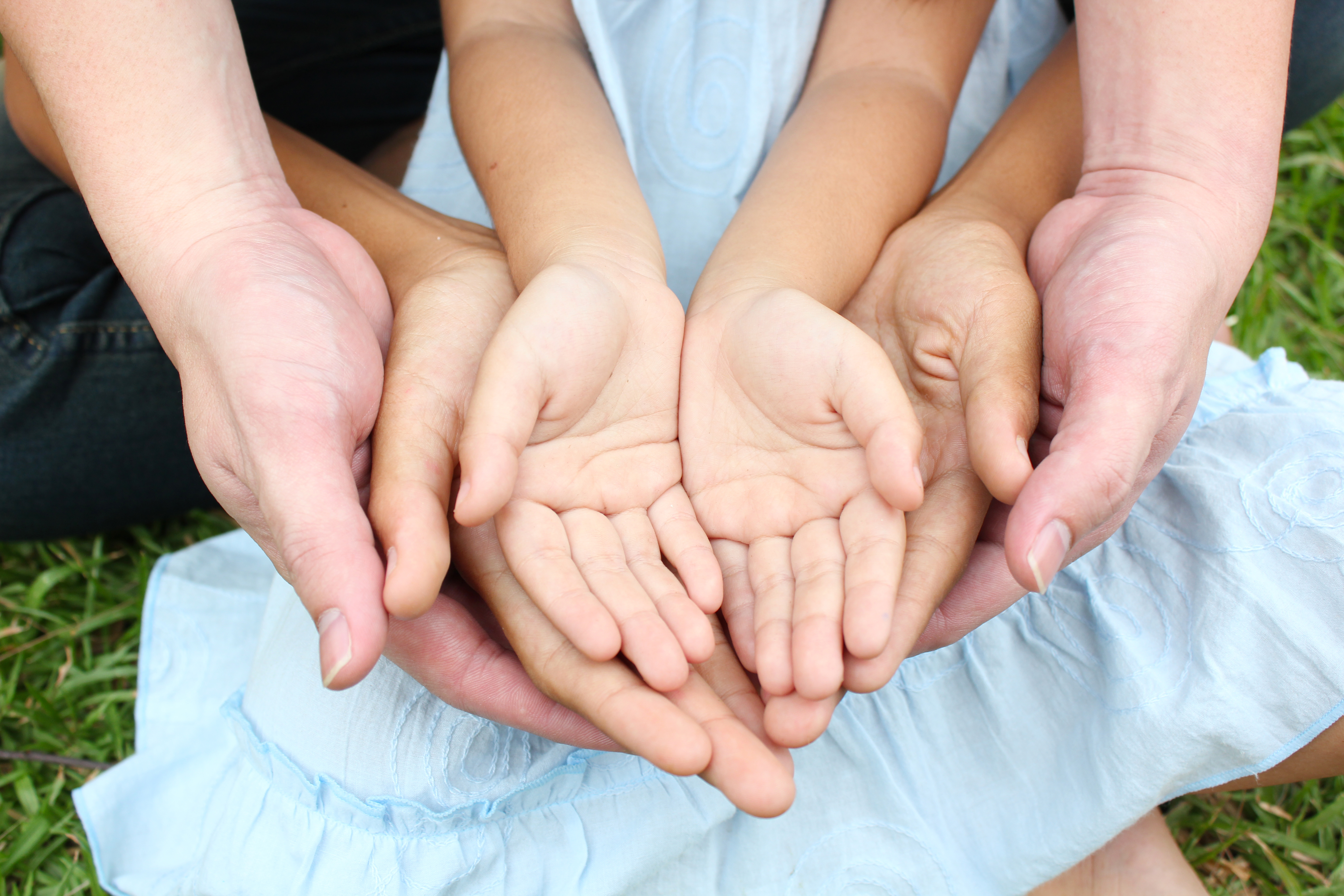 Child's hands in adult's hands