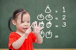 Asian child counting on hands in front of blackboard